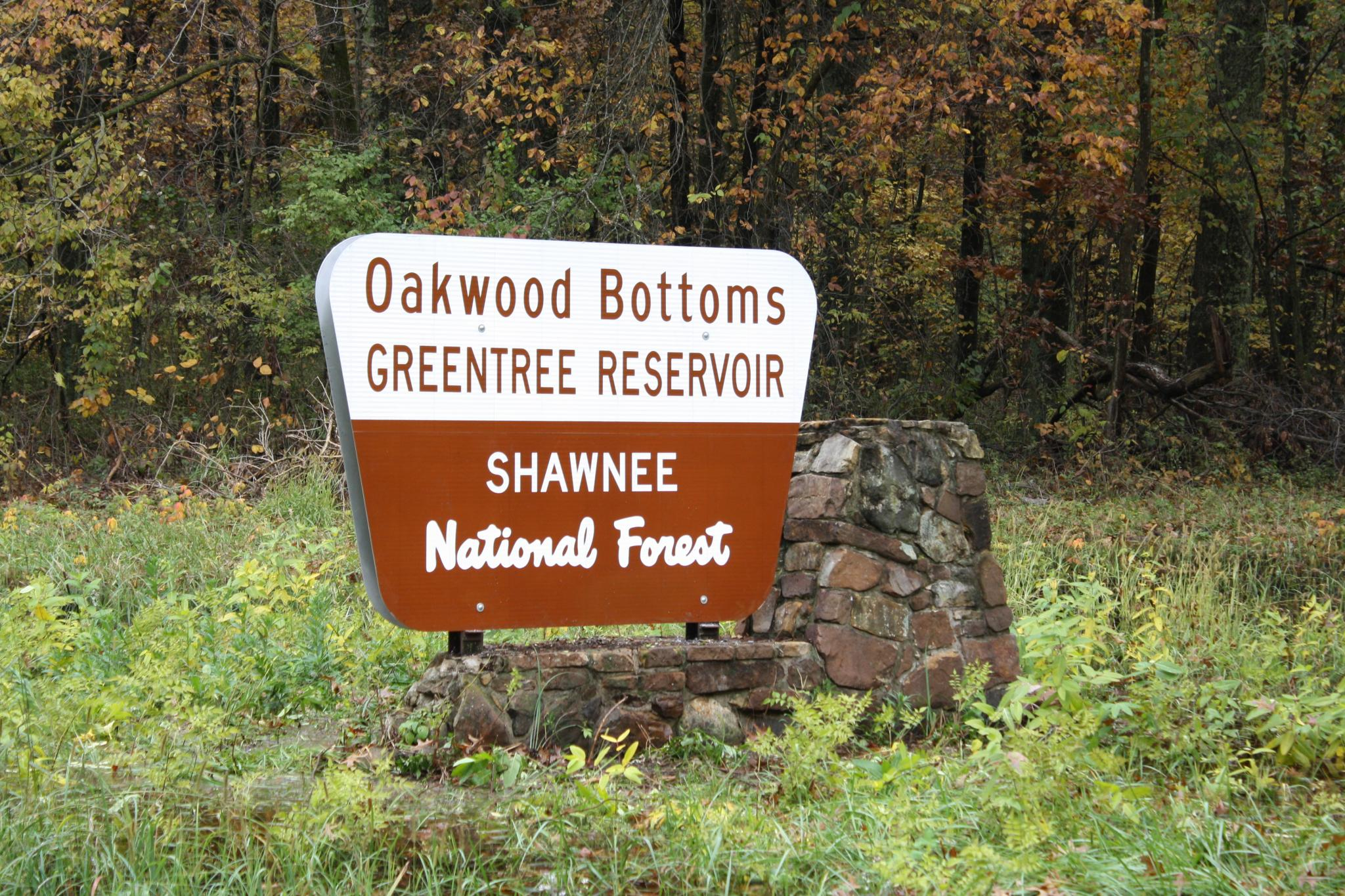 Oakwood Bottoms Greentree Reservoir Entrance sign. White on top brown on bottom.  surrounded by green grass.